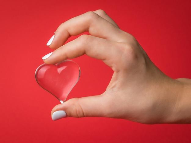 Le dita del bambino tengono delicatamente un cuore di vetro su fondo rosso. un simbolo di amore e vita. Foto Premium