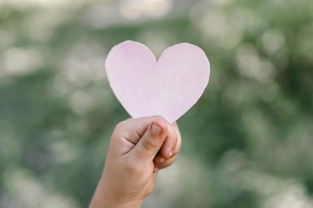 La mano del bambino tiene un cuore. Foto Premium