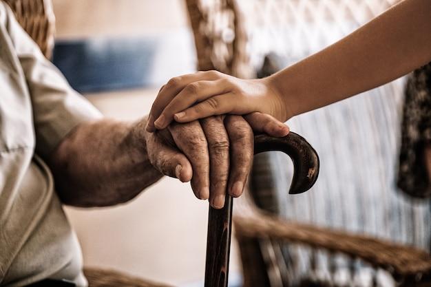 La mano del bambino sopra la mano dell'uomo anziano che tiene una canna. Foto Premium
