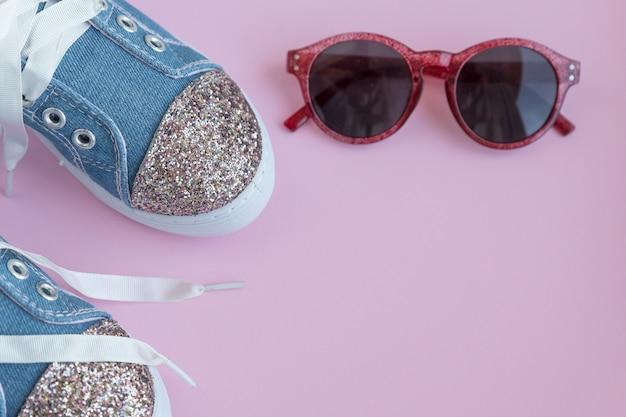 Sneaker in pizzo tessile per bambini. scarpe da ragazza sulla parete rosa. calzature per bambini alla moda. denim alla moda casual casual e scarpe lucide. scarpe sportive per bambini e alla moda. copi lo spazio. messa a fuoco selettiva Foto Premium