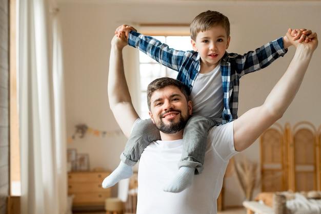 Bambino seduto sulle spalle di suo padre Foto Premium