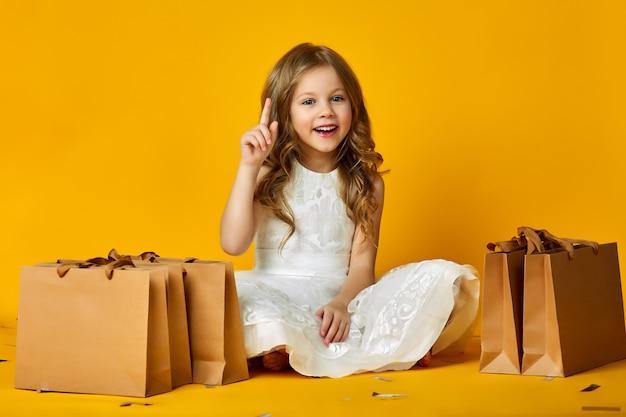 Sorriso del bambino con con i sacchetti di carta in negozio. Foto Premium