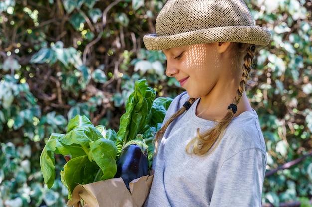 Bambino con cappello di vimini in estate con generi alimentari dal mercato eco-friendly Foto Premium