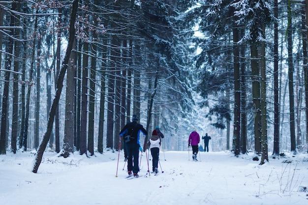 Bambini e adulti che sciano nei boschi come attività sportiva invernale Foto Premium