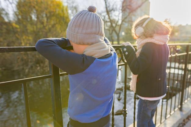 Bambini ragazzo e ragazza appoggiati sul ponte, guardando le anatre Foto Premium