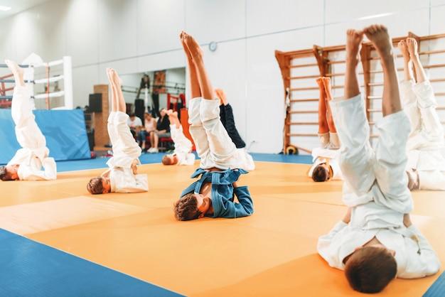 I bambini karate, i bambini in kimono praticano l'arte marziale in palestra. i ragazzini e le ragazze in uniforme fanno esercizio capovolto sull'allenamento sportivo Foto Premium
