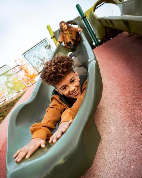 Bambini che giocano insieme su uno scivolo Foto Premium