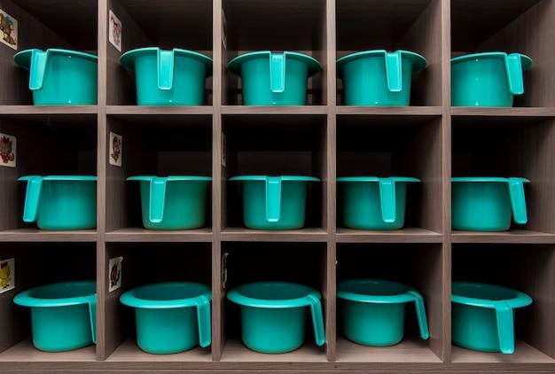 I vasi turchesi per bambini stanno in fila su un rack nell'asilo del bagno Foto Premium