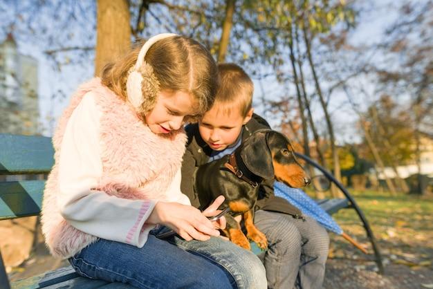 Bambini seduti su una panchina nel parco con il cane, guarda lo smartphone. Foto Premium