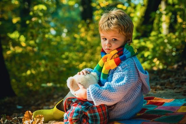 Amicizia dei bambini. divertimento autunnale al parco. bambini felici in autunno. ragazzo carino con foglie d'autunno in autunno Foto Premium