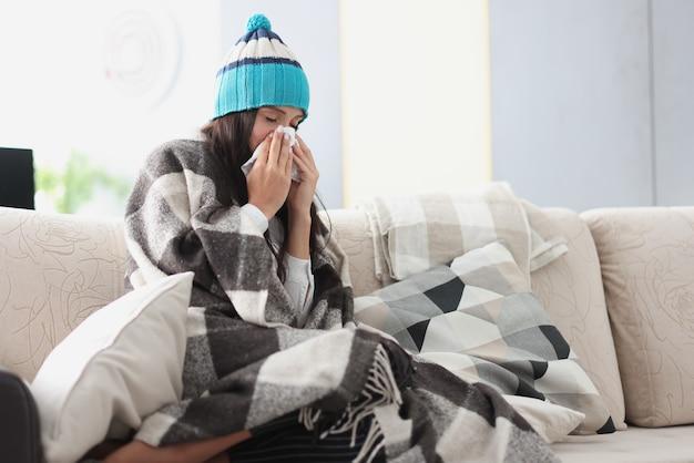 Donna raffreddata sul divano in coperta e cappello tiene il fazzoletto Foto Premium