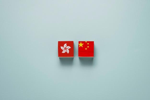 Bandiere di cina e hong kong stampano lo schermo su blocchi di cubi di legno. hong kong e cina conflitto politico e concetto di protesta. Foto Premium