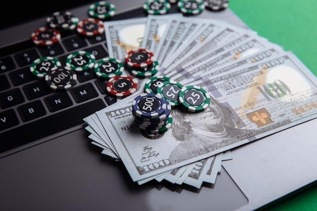 Chip, banconote e laptop per il primo piano di gioco d'azzardo in linea o del casinò del poker. concetto di poker online. Foto Premium