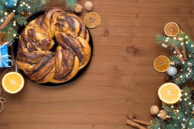 Nonna di natale al cioccolato a forma di ghirlanda con sciroppo d'arancia su un piatto tagliato a pezzi. decorazioni natalizie su un tavolo di legno. Foto Premium