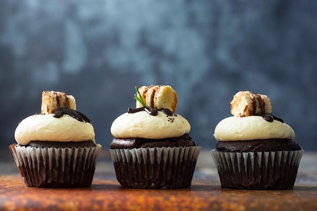 Cupcakes al cioccolato con crema al burro. dessert dolce, panetteria, dessert di pasticceria. Foto Premium