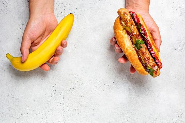La scelta di cibo sano e concetto di cibo malsano. vegano vs farina di carne. banana e hot dog in mani maschili. Foto Premium