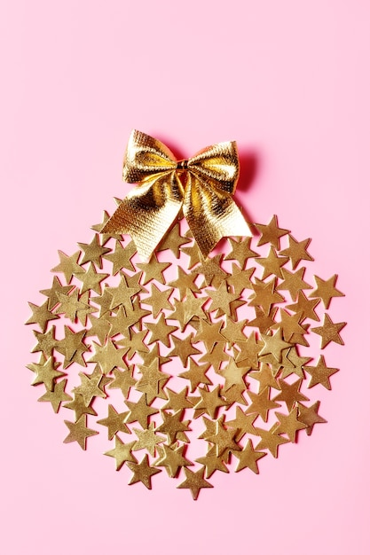 Disposizione di natale con stelle dorate e fiocco sulla superficie rosa Foto Premium
