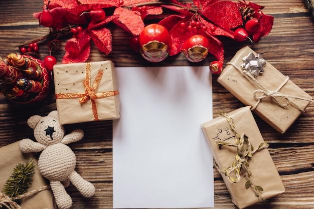 Sfondo di natale con carta artigianale, confezione regalo, giocattoli di natale fatti a mano. vista dall'alto sulla scrivania in legno. ornamento e regalo di natale. lettera di babbo natale. Foto Premium