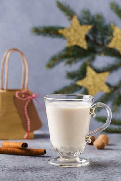 Sfondo di natale con, scatole regalo, stelle, decorazioni festive, abete, bastoncini di cannella, bevanda calda allo zabaione. Foto Premium