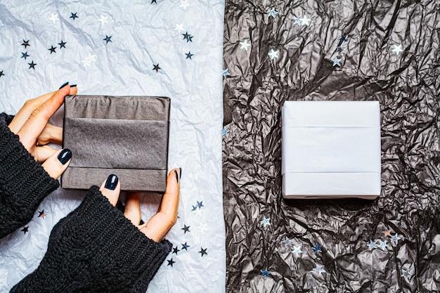 Sfondo bianco e nero di natale con scatole regalo e stelle di coriandoli. concetto di natale. Foto Premium