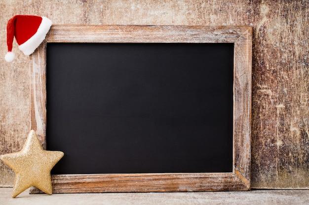 Lavagna e decorazione di natale sopra la tavola di legno. Foto Premium