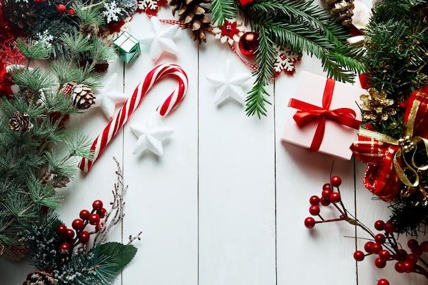Composizione di natale. regali, rami di abete, decorazioni rosse su fondo bianco. natale, inverno, concetto di capodanno. Foto Premium
