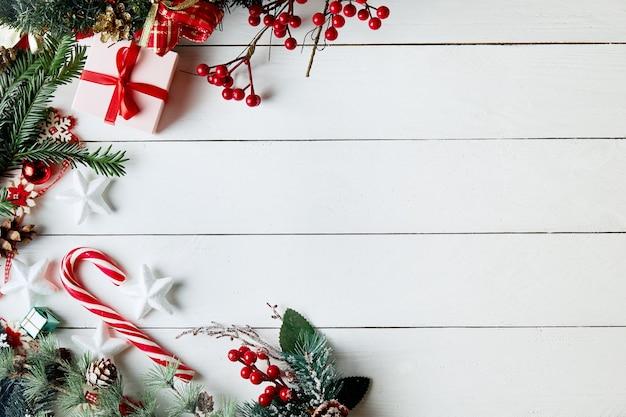 Composizione di natale. regali, rami di abete, decorazioni rosse su fondo bianco. Foto Premium