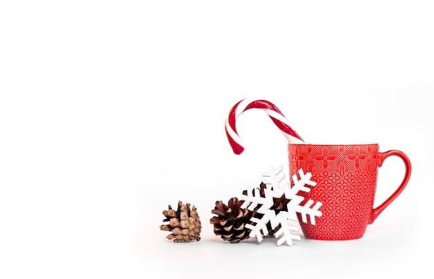 Composizione in natale con tazza rossa, pigne e fiocco di neve Foto Premium