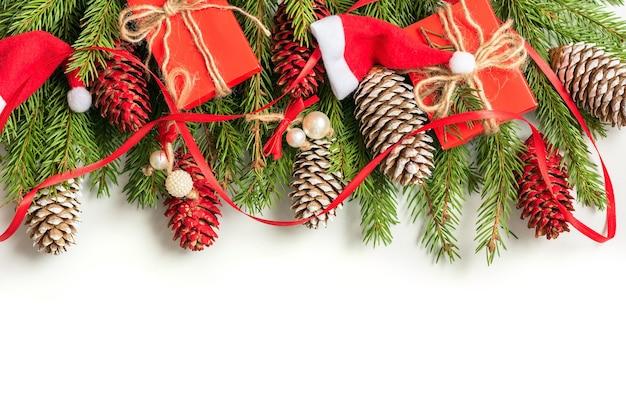 Concetto di natale di decorazioni fatte di rami di abete e coni su uno sfondo isolato. Foto Premium