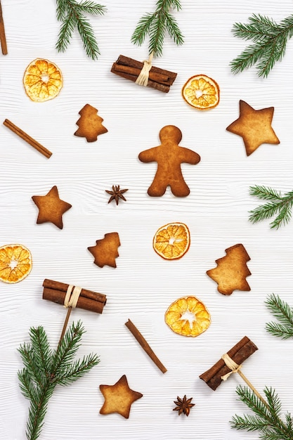Biscotti di natale assortiti vista dall'alto, rami di abete verde, bastoncini di cannella, arance secche Foto Premium