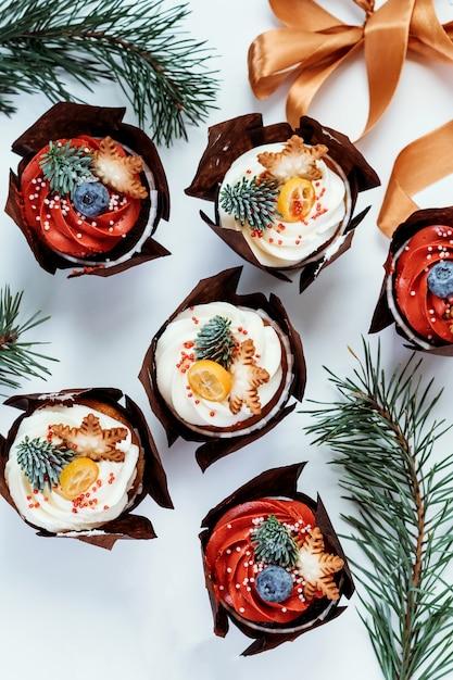 Cupcakes di natale per la decorazione di capodanno. set di pasticcini decorati con bacche, stelle e rami di abete. Foto Premium