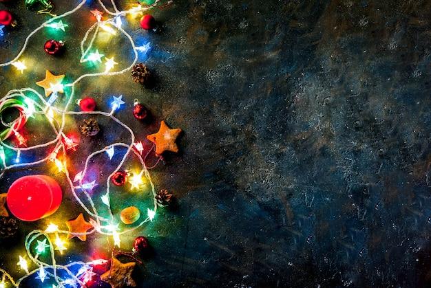 Sfondo scuro di natale con ghirlanda di natale, decorazioni, stelle di panpepato e candele. vista dall'alto copia spazio Foto Premium