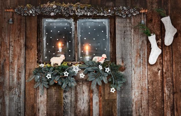 Decorazioni natalizie di pareti in legno e finestre in stile rustico. rami di conifere e calzini bianchi a lume di candela attraverso la finestra accogliente. Foto Premium