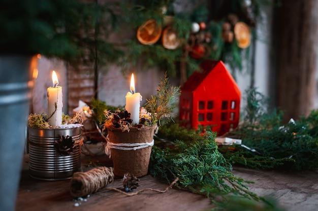 Candele fatte a mano con decorazioni natalizie. alberi di natale tessili fatti a mano per una tavola festiva con le tue mani. Foto Premium