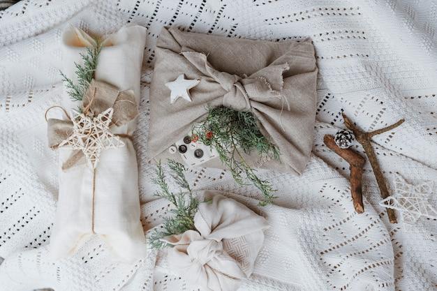 Carta da regalo ecologica natalizia in tradizionale stile furoshiki giapponese su una parete bianca lavorata a maglia. incartare regali con le tue mani. capodanno economico. Foto Premium