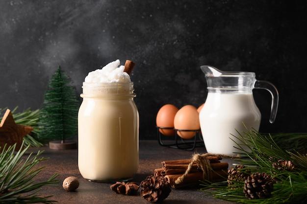 Zabaione di natale in barattolo di vetro con ingredienti su sfondo marrone scuro. avvicinamento. Foto Premium