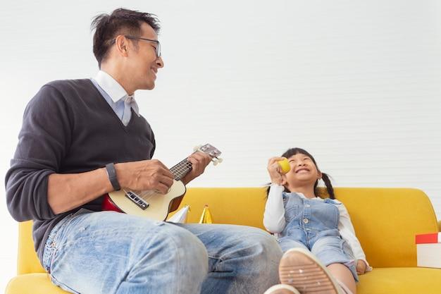 La famiglia di natale e le feste felici generano suonare la chitarra vicino al regalo attuale con i bambini al salone bianco. Foto Premium