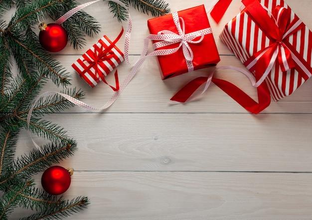 Sfondo festivo di natale, bellissimi regali con nastri e fiocchi, rami di abete verde con decorazioni natalizie su un fondo di legno bianco Foto Premium
