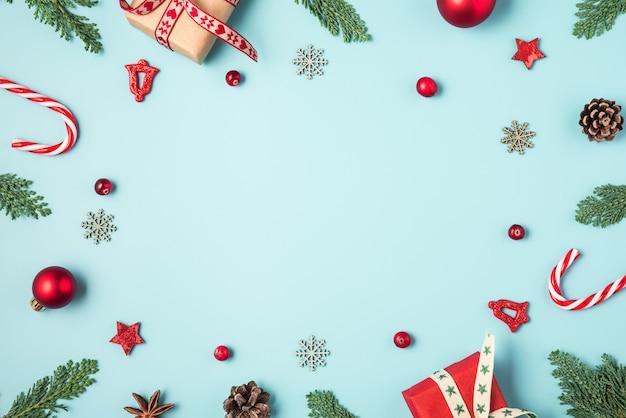 Cornice di natale fatta di rami di abete, scatole regalo, caramelle, decorazioni vacanza rosso e pigne su sfondo blu Foto Premium