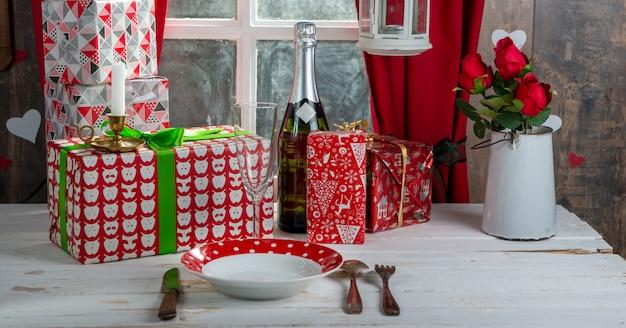 Regali di natale sulla tabella vicino alla finestra rustica Foto Premium