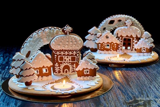 Casa di pan di zenzero di natale con una candela accesa Foto Premium