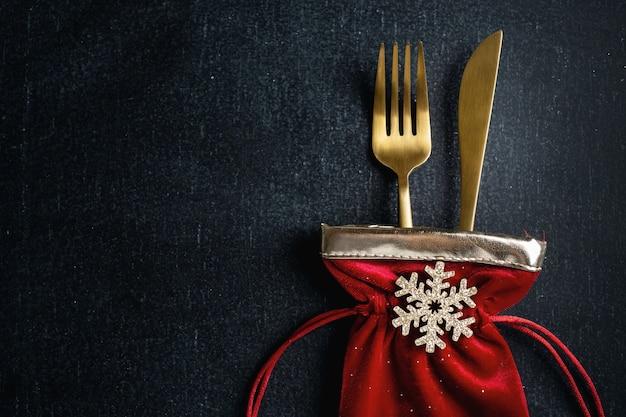 Posate di natale d'oro in piccola borsa in tessuto con fiocco di neve e nastro su sfondo scuro. Foto Premium