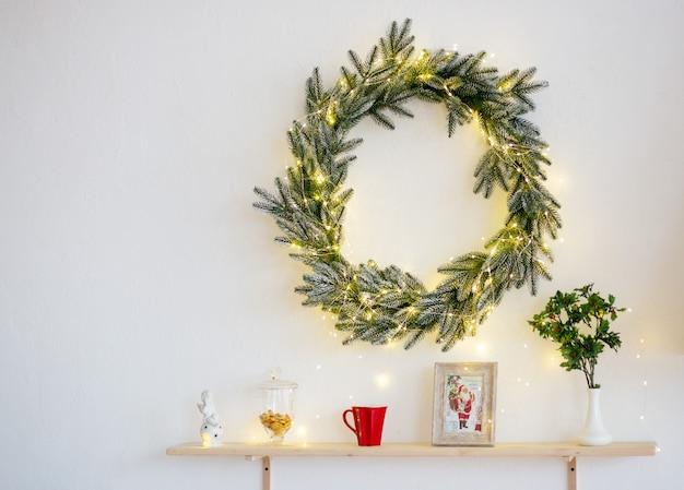 Ghirlanda di natale verde e altre decorazioni, a luci gialle su sfondo bianco Foto Premium