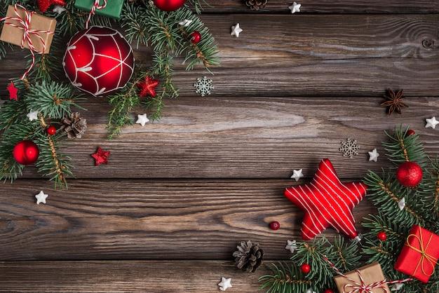 Sfondo di natale e felice anno nuovo rami di albero di abete con decorazioni rosse sulla tavola di legno Foto Premium