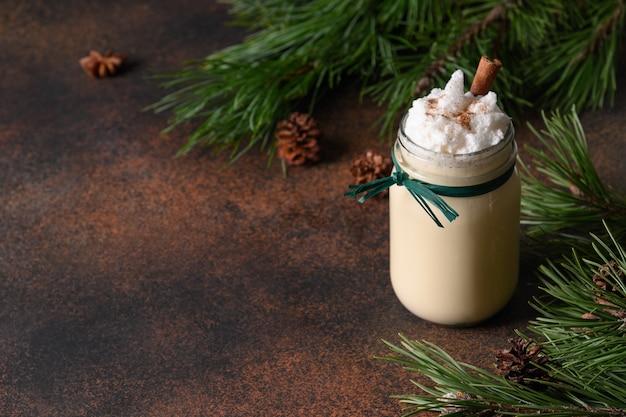 Zabaione di festa di natale in barattolo di vetro con l'albero di abete decorato cannella su fondo marrone Foto Premium