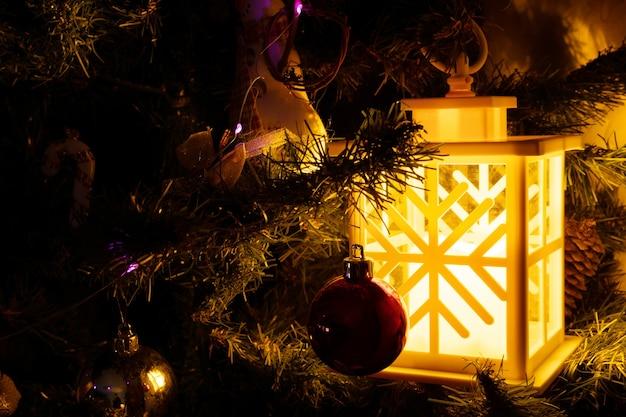 Una lanterna di natale con un'accogliente luce calda è appesa a un ramo di abete Foto Premium