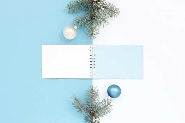 Superficie di festa di natale azzurro e bianco con blocco note e decorazioni Foto Premium