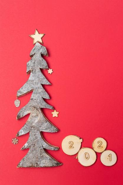 Cartolina di natale e capodanno con numeri in legno 2021 e albero di natale in legno su sfondo rosso. Foto Premium