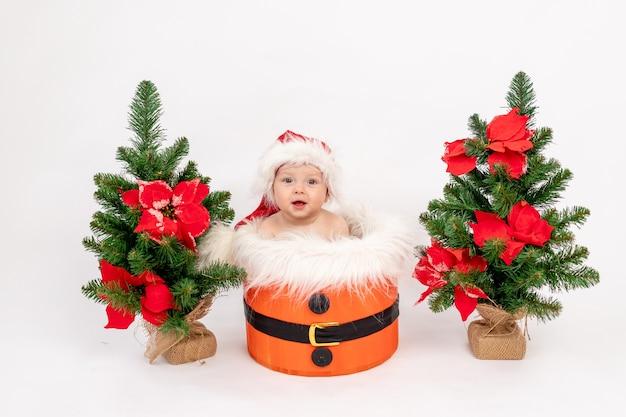 Foto di natale una bambina piccola seduta in un cappello da babbo natale in un cesto vicino agli alberi di natale Foto Premium