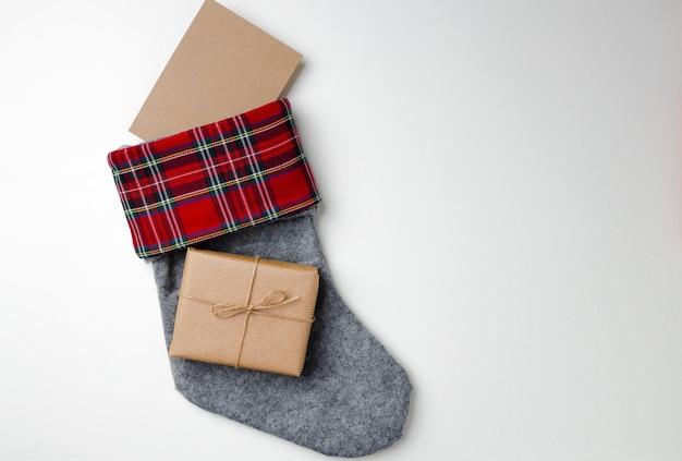 Calza di natale con regalo avvolto su bianco Foto Premium